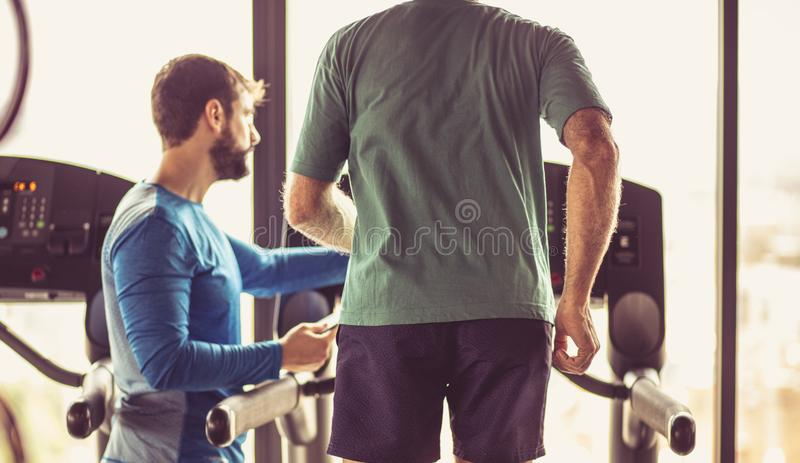 Let`s just go, calories must disappear. Personal trainer giving support senior men during exercise stock images
