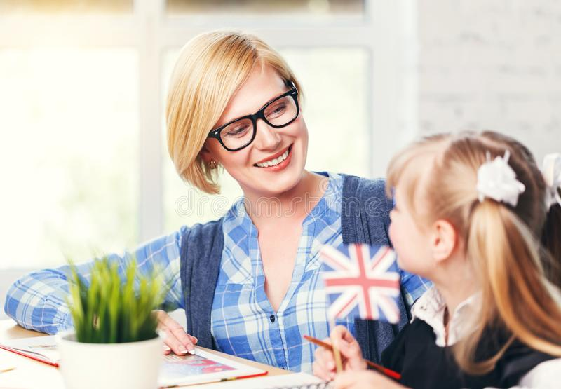 Let`s Learn English. Smiling blonde English educator wears eyeglasses studying with kid girl, language learning with children in white light classroom stock photography