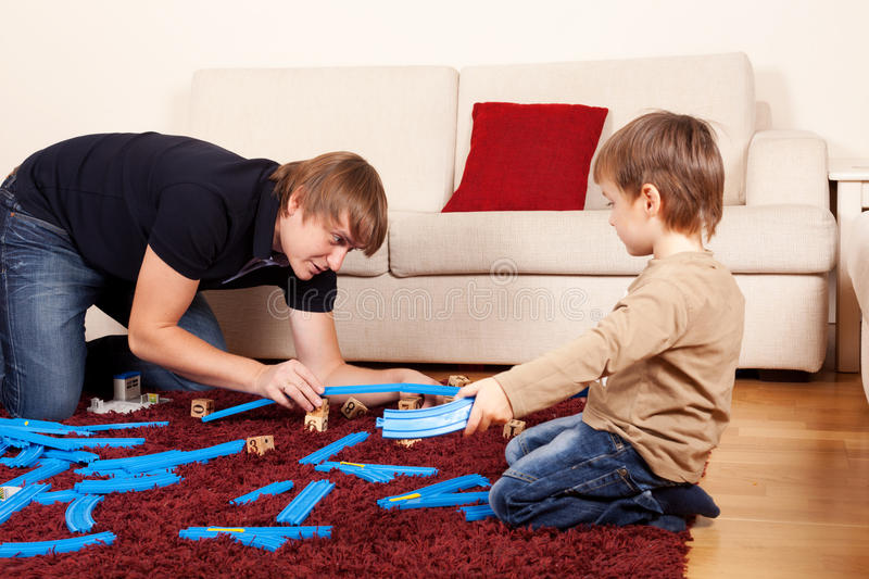 Let's play. Father is playing with son in toy railroad royalty free stock image