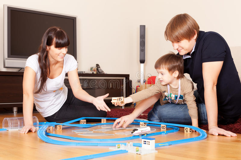 Let's play. Family is playing toy railroad and bricks stock photo