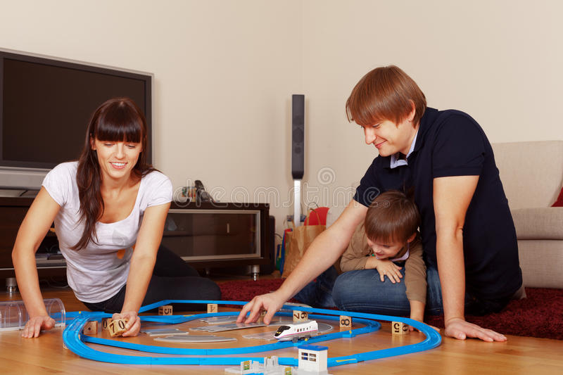 Let's play. Family is playing toy railroad and bricks royalty free stock image