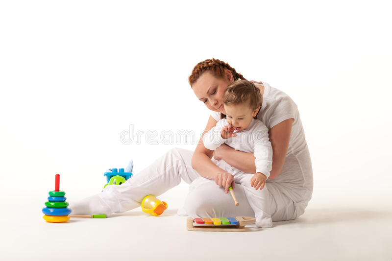 Let's play. Mother is showing son how to play xylophone stock photography