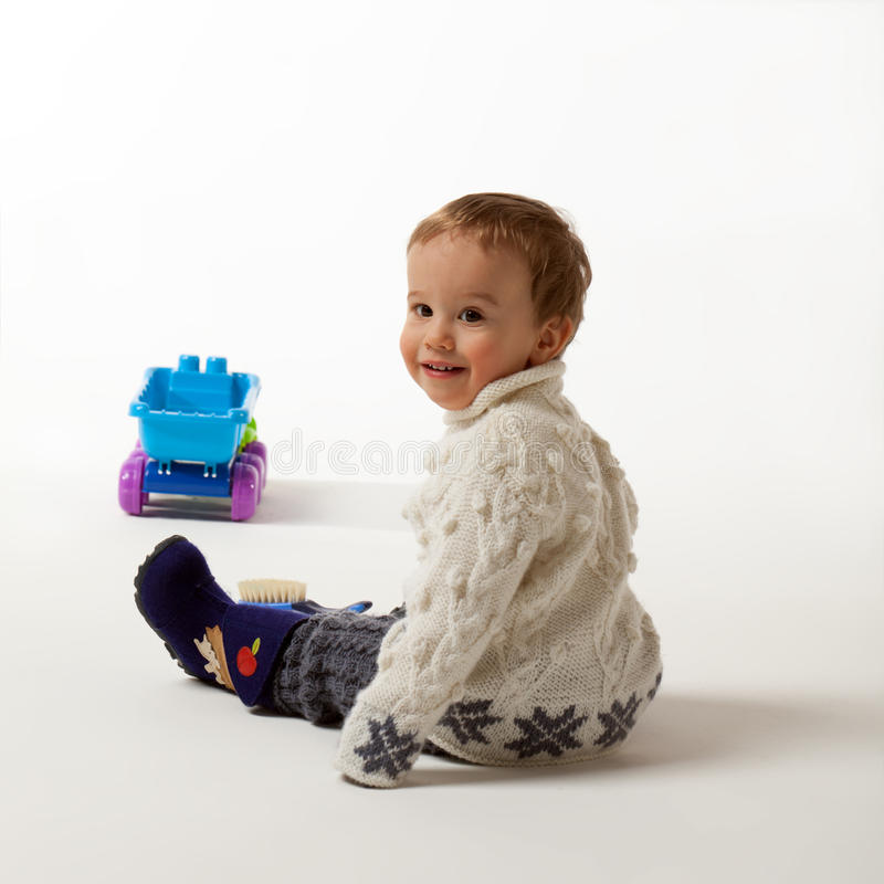 Let's play. Little boy is looking over shoulder inviting to play royalty free stock photo