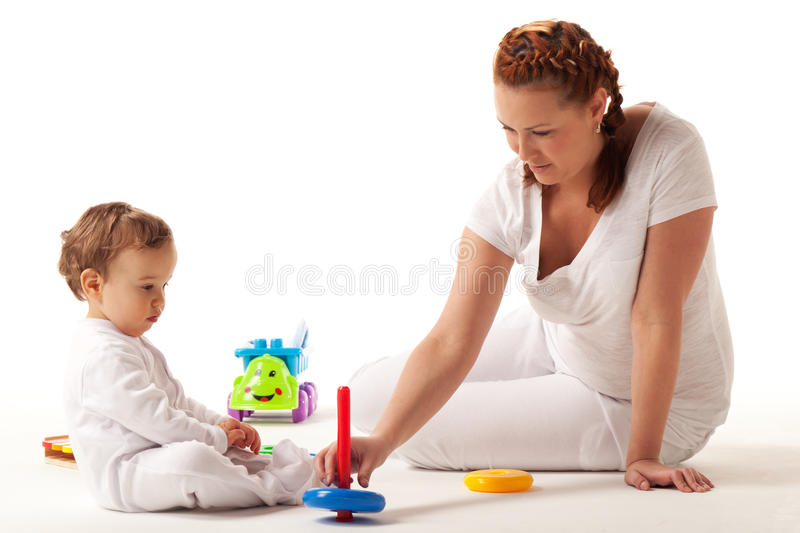 Let's play. Mother shows son how to build pyramid royalty free stock image