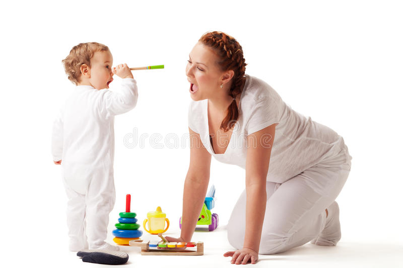 Let's play. Mother is showing son how to play xylophone royalty free stock image