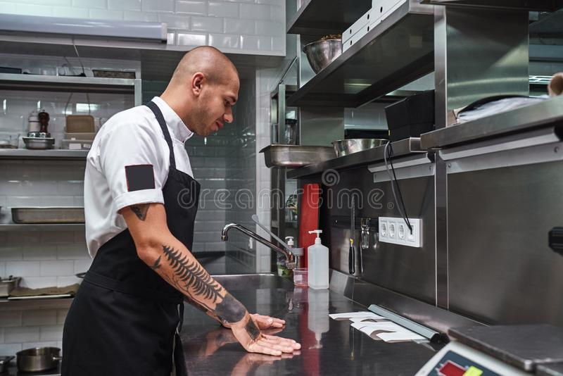 Let`s start. Young bald male chef with beautiful tattoos on his arms looking at order lists on a steel table in a. Restaurant kitchen. Side view. Cooking stock photography