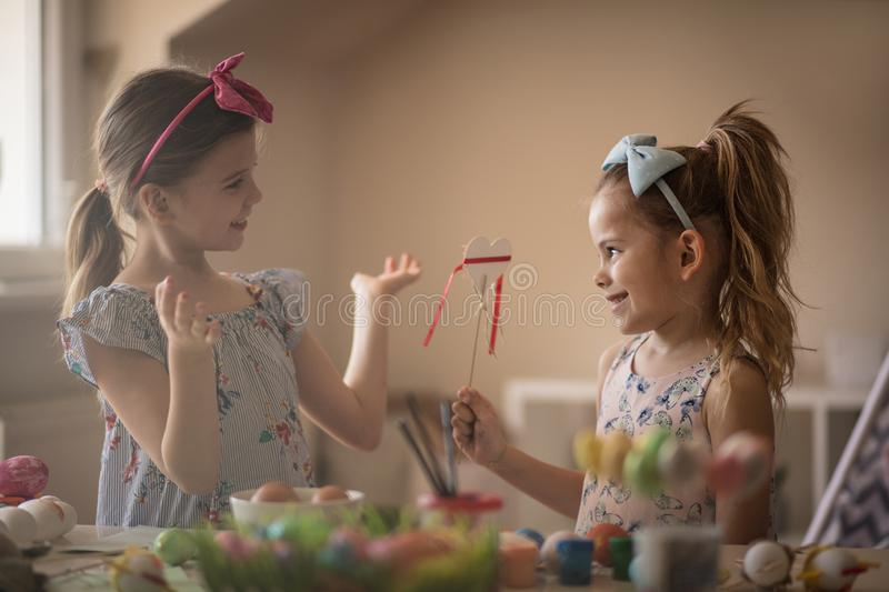 Let`s talk about Easter gifts. Little girls coloring Easter egg stock photography