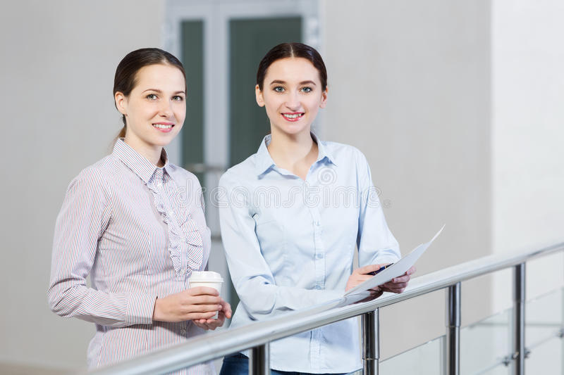 Let's talk it over. Two women standing at balcony and having dialogue stock photography