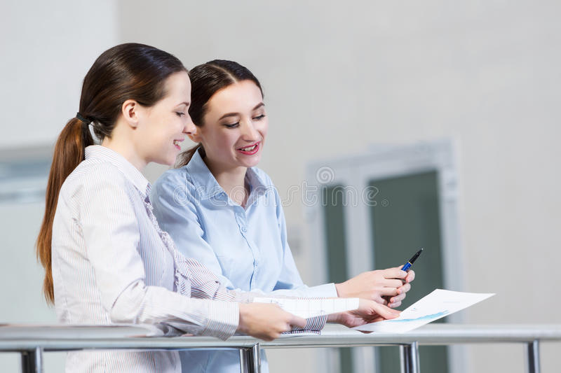 Let's talk it over. Two women standing at balcony and having dialogue royalty free stock photos