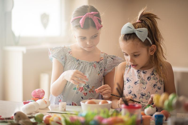 Let them be as creative as they want to. Little girls coloring Easter egg stock photography