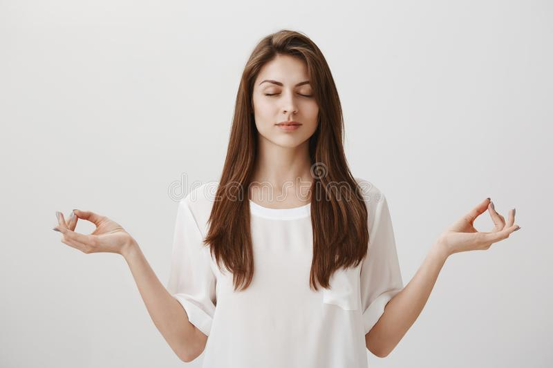 Let there be calm. Portrait of focused relaxed attractive female with closed eyes, happy smile, meditating with spread royalty free stock image