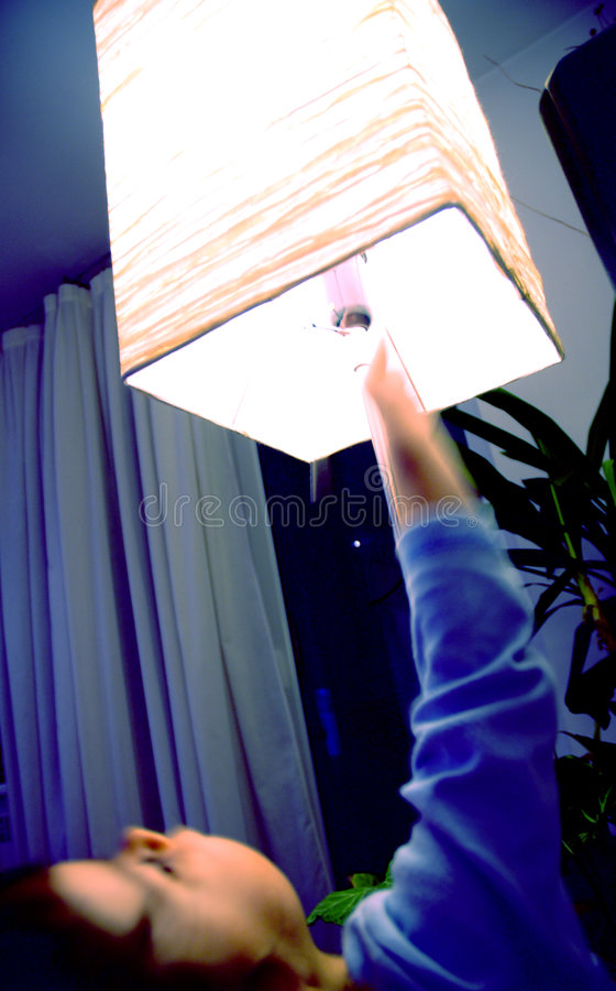 Let there be light. Kid switching the light on. Blue tones enhanced digitallly. Subject is motion blurred