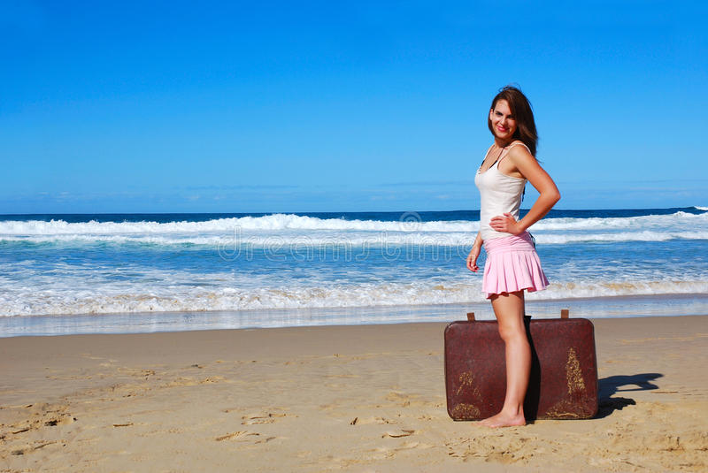 Let us go on holidays. A beautiful Caucasian young woman with happy smiling facial expression standing with her suitcase on the beach in front of the sea at her
