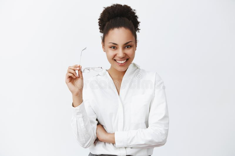 Let us talk about business. Charming confident and friendly-looking successful female entrepreneur with dark skin and. Curly hair, taking off glasses, gazing royalty free stock photography