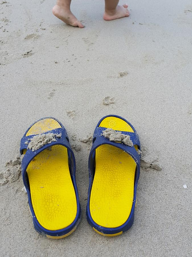 Let va palabra en la playa y la sandalia amarilla fotografía de archivo