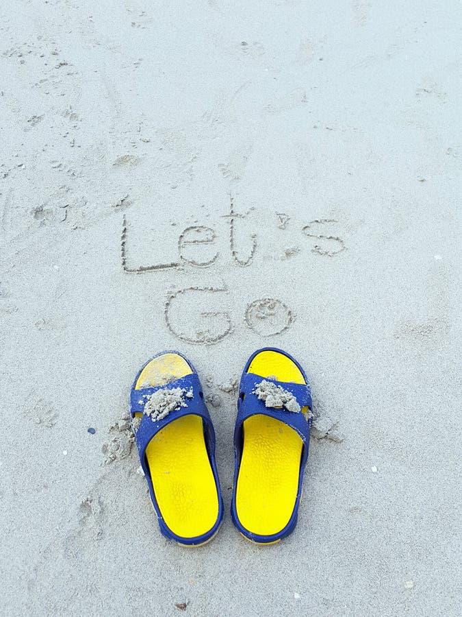 Let va palabra en la playa y la sandalia amarilla fotos de archivo libres de regalías