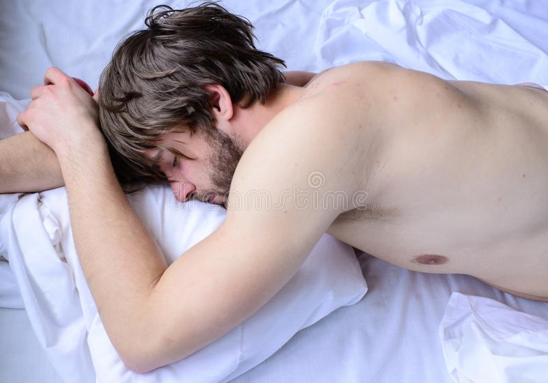 Let your body feel comfortable. Guy nude macho lay white bedclothes. Man sleepy drowsy unshaven bearded face having rest. Pleasant relax concept. Man unshaven royalty free stock images