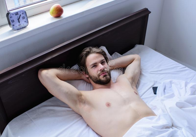 Let your body feel comfortable. Man unshaven handsome guy naked torso relaxing bed. Guy macho lay white bedclothes. Man sleepy drowsy unshaven bearded face stock photos