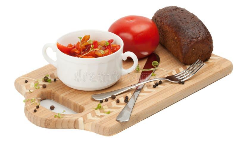 Letcho, tomates, pan negro en una tabla de cortar imagenes de archivo