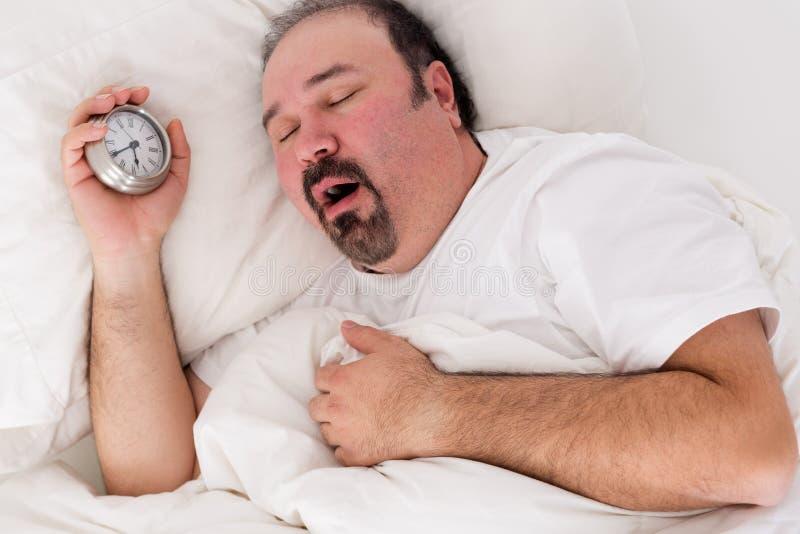 Lethargic man yawning as he struggles to wake up. Lethargic tired man lying in bed yawning as he struggles to wake up unmotivated to start the new day and stock photo
