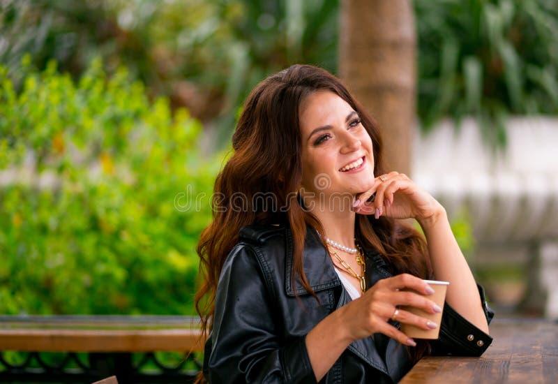 lether夹克的俏丽的快乐的年轻女人坐从纸杯的咖啡馆大阳台饮用的咖啡 o 库存图片