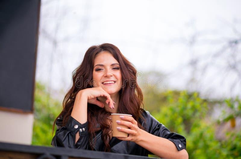 lether夹克的俏丽的快乐的年轻女人坐从纸杯的咖啡馆大阳台饮用的咖啡 o 库存照片