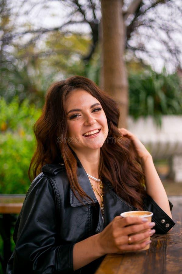lether夹克的俏丽的快乐的年轻女人坐从纸杯的咖啡馆大阳台饮用的咖啡 o 图库摄影
