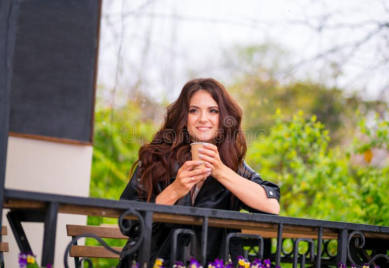 lether夹克的俏丽的快乐的年轻女人坐从纸杯的咖啡馆大阳台饮用的咖啡 o 免版税库存照片