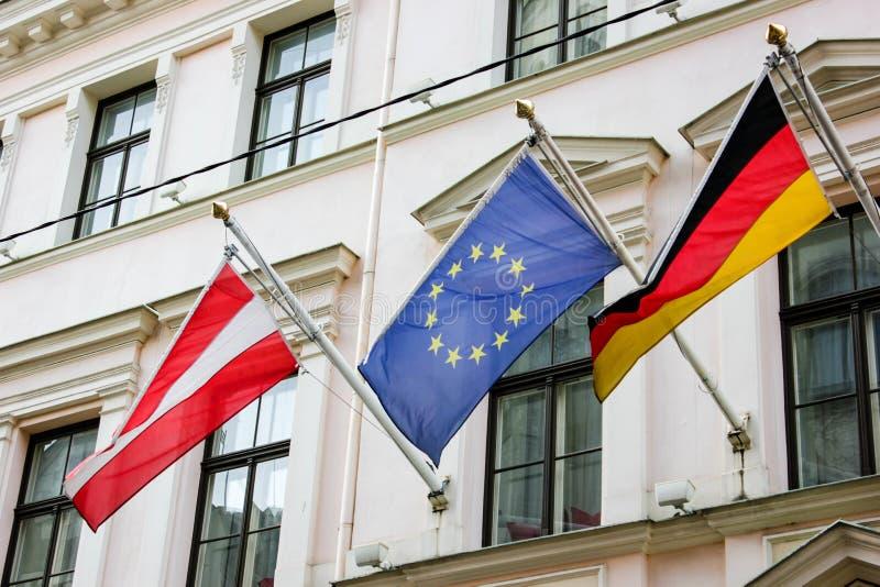 Letland, Europese Unie en de vlaggen van Duitsland op een neutrale achtergrond stock afbeelding