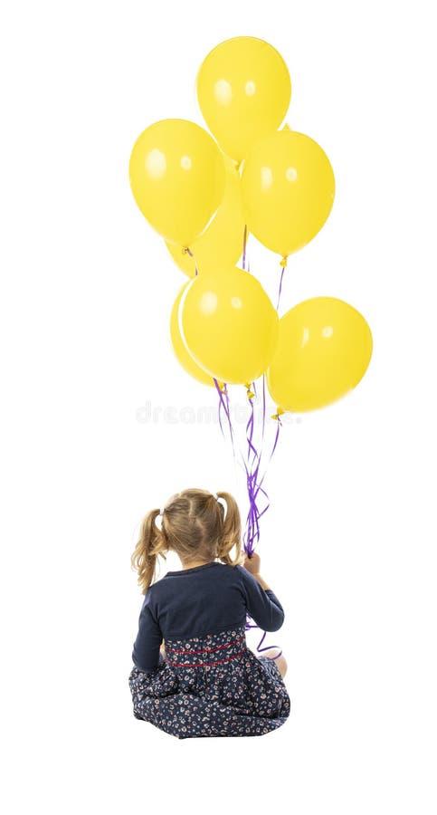 3-letnia dziewczynka trzymająca grupę żółtych balonów obraz royalty free