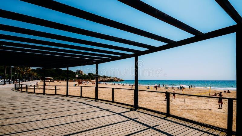 Letnicy w Arrabassada plaży, jeden sławny złoty piasek wyrzucać na brzeg w Hiszpańskim Costa Daurada zdjęcie royalty free
