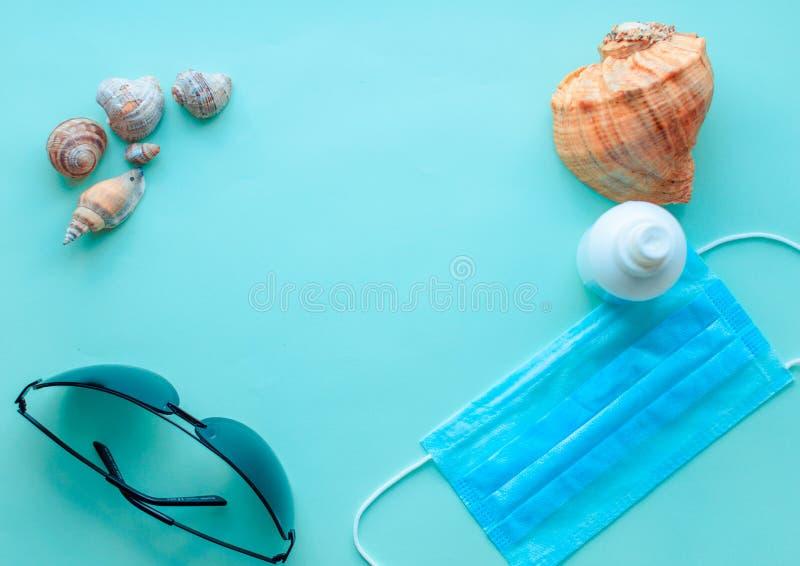 Letnie wakacje, wypoczynek na plaży i maska ochronna, rękawice, antyseptyczne na miętowym niebieskim tle Podróże Coronavirus covi zdjęcie stock