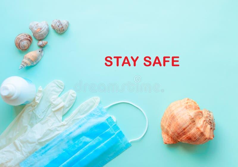 Letnie wakacje, wypoczynek na plaży i maska ochronna, rękawice, antyseptyczne na miętowym niebieskim tle Podróże Coronavirus covi zdjęcia stock