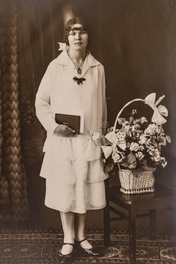 LETONIA - CIRCA los años 30: Un retrato de la mujer joven en el estudio, foto del vintage foto de archivo libre de regalías