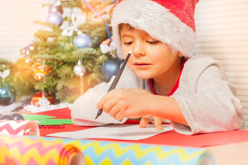Letra bonito da escrita do rapaz pequeno a Papai Noel fotografia de stock