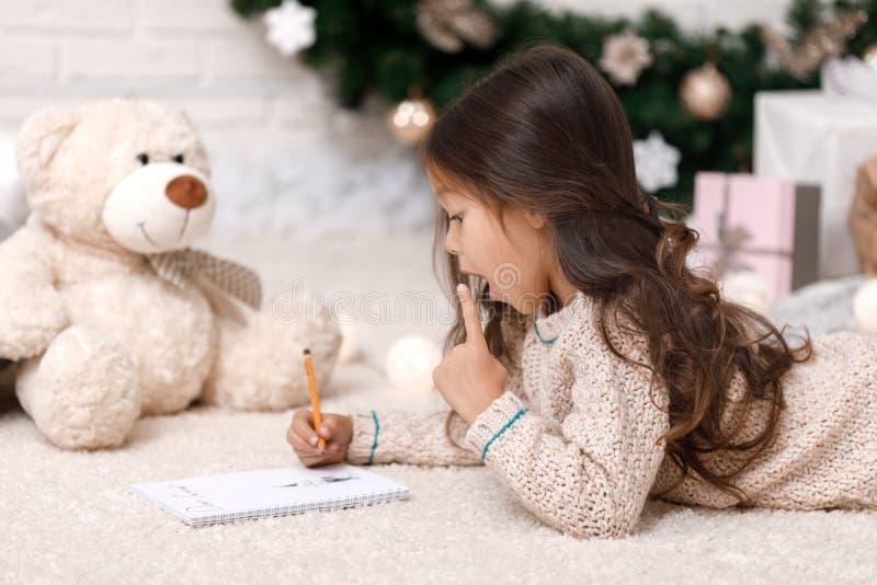 Letra bonito da escrita da menina da criança a Santa Claus em casa fotos de stock