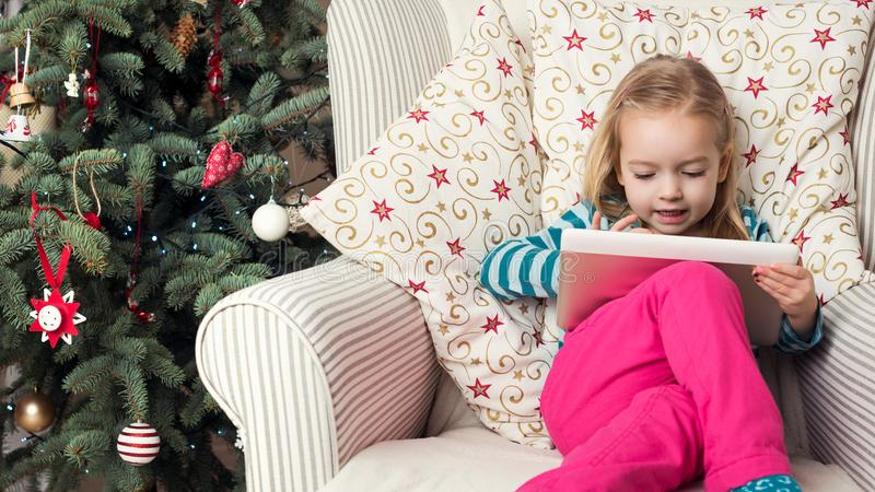 Letra bonito a Santa na tabuleta digital, assento da escrita da menina na frente da árvore do xmas imagens de stock royalty free