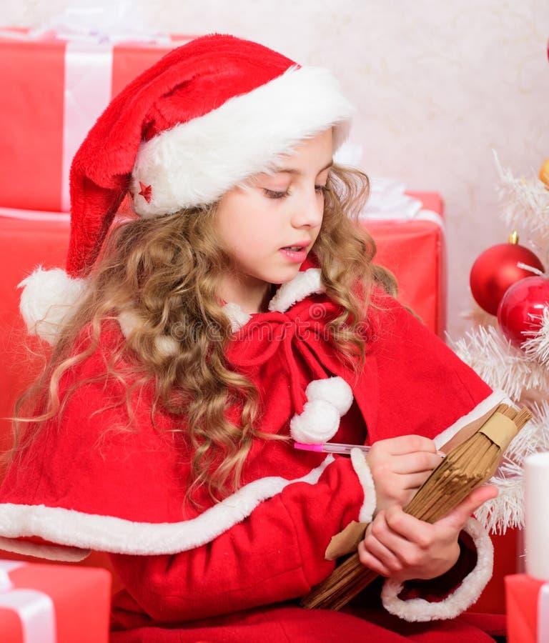Letra da escrita da criança a Santa Claus Cara Santa Pena e papel bonitos pequenos da posse da criança da menina perto da árvore  fotos de stock royalty free