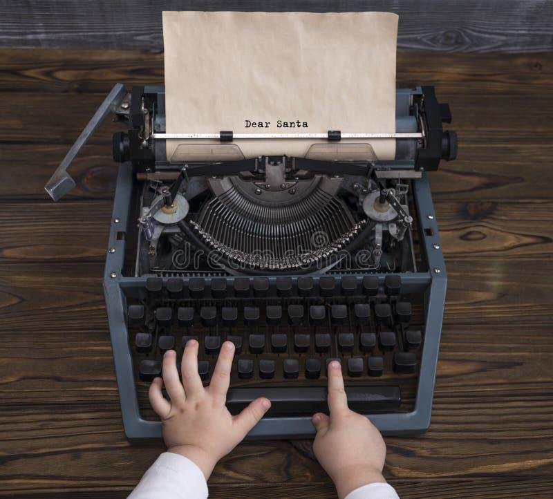 Letra da escrita da mão do ` s da criança a Santa Claus na máquina de escrever do vintage em antecipação ao feriado do Natal imagens de stock