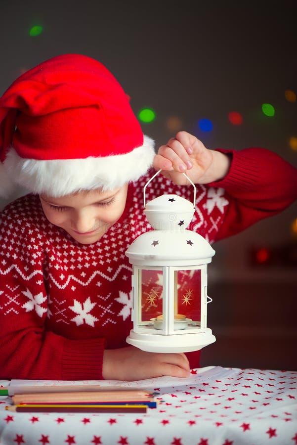 Letra de la escritura del niño de la Navidad a la letra de Santa Claus en sombrero rojo imagen de archivo