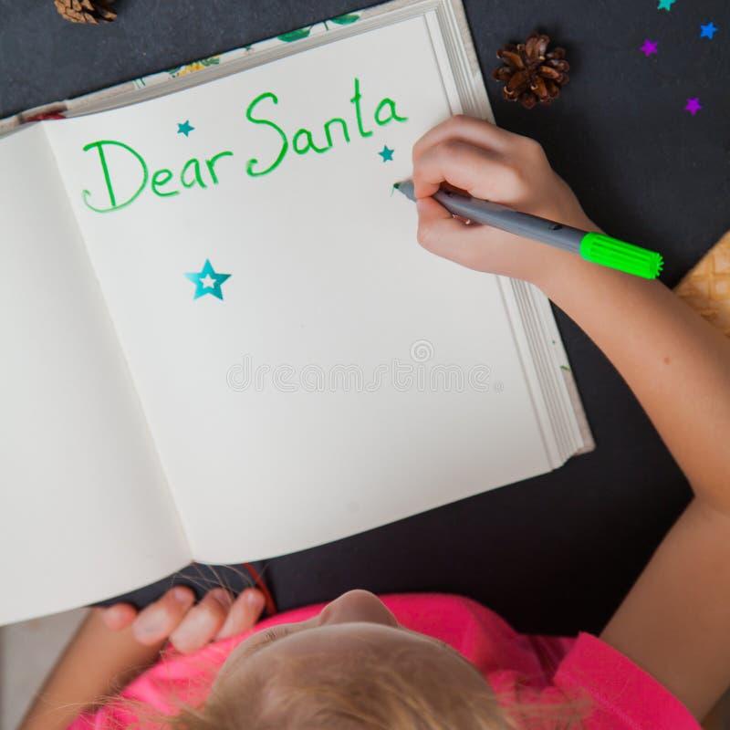 Letra de la escritura del pequeño niño a Santa Claus en una hoja de papel en blanco imagen de archivo libre de regalías