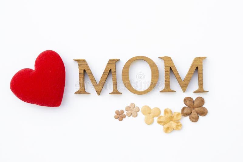 Letra de madeira da textura da mamã com flor de papel e isolado vermelho do coração no fundo branco imagens de stock royalty free