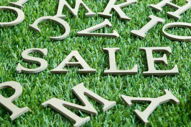 Letra de madera en venta de la palabra en hierba verde artificial con el fondo del alfabeto inglés imagen de archivo libre de regalías