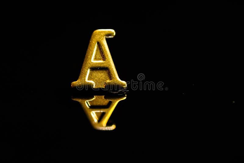 Letra de oro A con la reflexi?n en un fondo negro fotos de archivo
