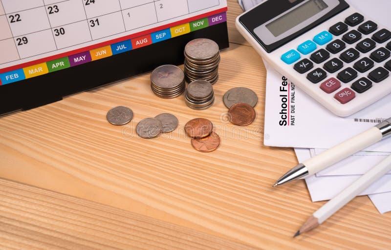 Letra del aviso de la tarifa de la escuela, tarifa de la educación, calendario de escritorio, calculadora, moneda del dinero, plu fotografía de archivo libre de regalías