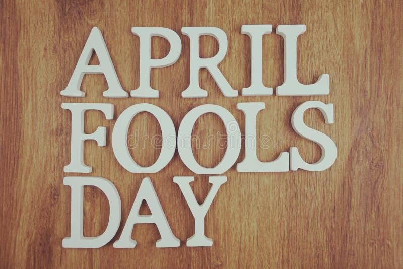 Letra do alfabeto do dia do enganado com cópia do espaço no fundo de madeira fotografia de stock royalty free