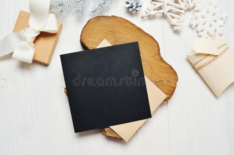 Letra do cartão do preto do Natal do modelo no envelope e presente com a árvore branca, flatlay em um fundo de madeira branco imagens de stock royalty free