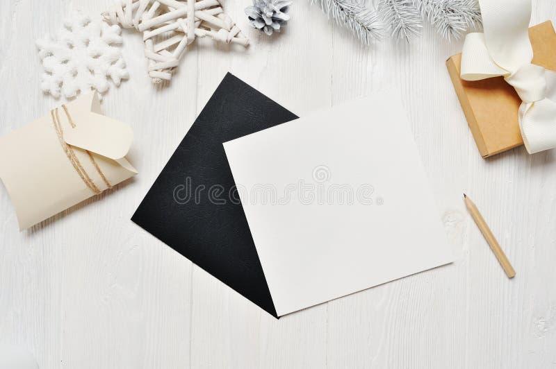 Letra do cartão do preto do Natal do modelo no envelope e presente, flatlay em um fundo de madeira branco, com lugar para imagem de stock