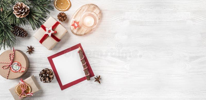 Letra do Natal para Santa no fundo branco com presentes, lápis, ramos do abeto, cones do pinho, vela Tema do Xmas e do ano novo f imagem de stock