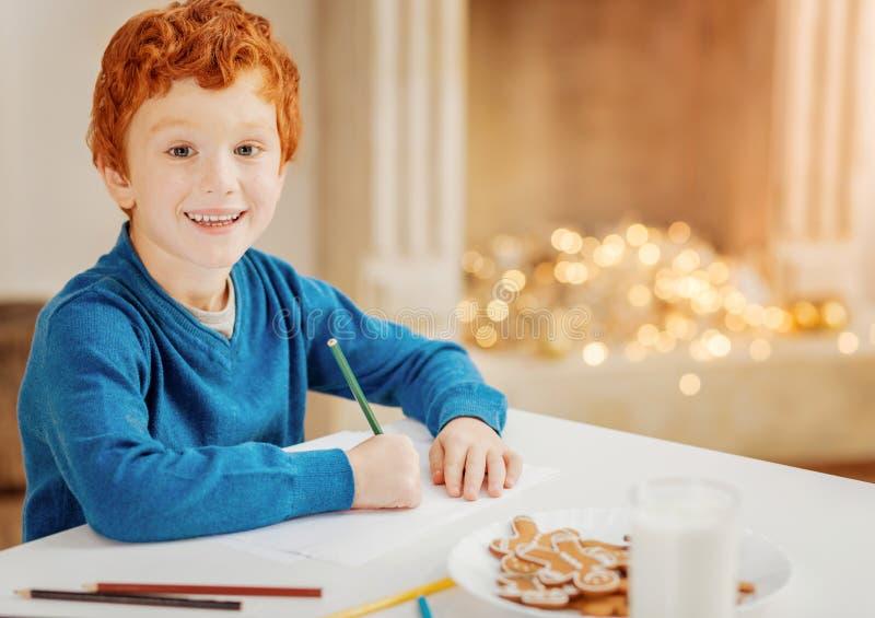 Letra emocionada de la escritura del niño pequeño a Papá Noel fotos de archivo libres de regalías